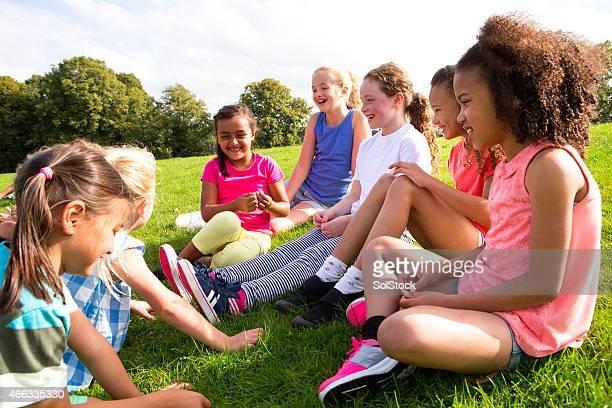 large group of children sitting on the grass - only girls stock pictures, royalty-free photos & images