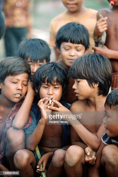 A large group of children trying to smoke on the streets of Phnom Penh Cambodia