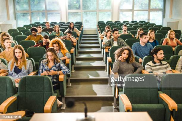 large group of college students attending a class in amphitheater. - amphitheater stock photos and pictures