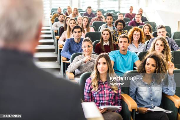 large group of college students listening to their professor on a class. - university stock pictures, royalty-free photos & images