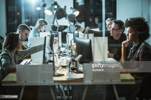 large group of computer programmers working late at corporate office. - nova empresa imagens e fotografias de stock