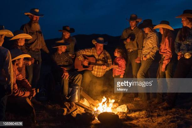 large group of cowboys singing and playing guitar at campfire - country and western music stock pictures, royalty-free photos & images