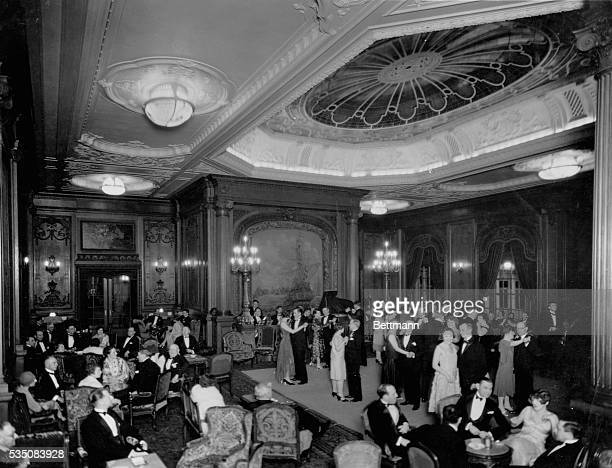 A large group of elegantly dressed couples dance and share casual conversation in an extravagant ballroom