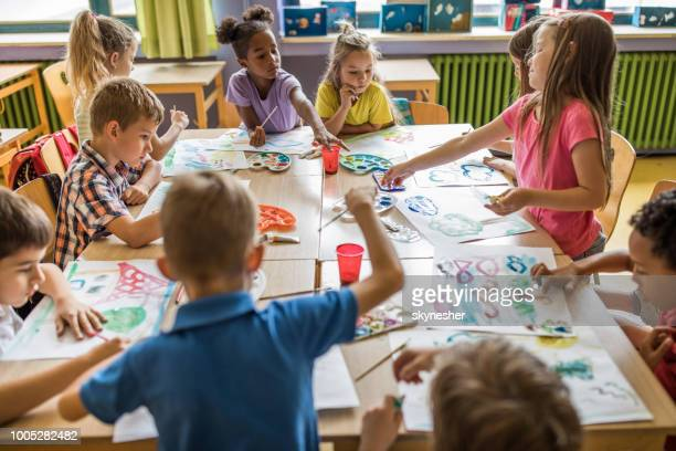 large group of elementary students having an art class in the classroom. - arti e mestieri foto e immagini stock