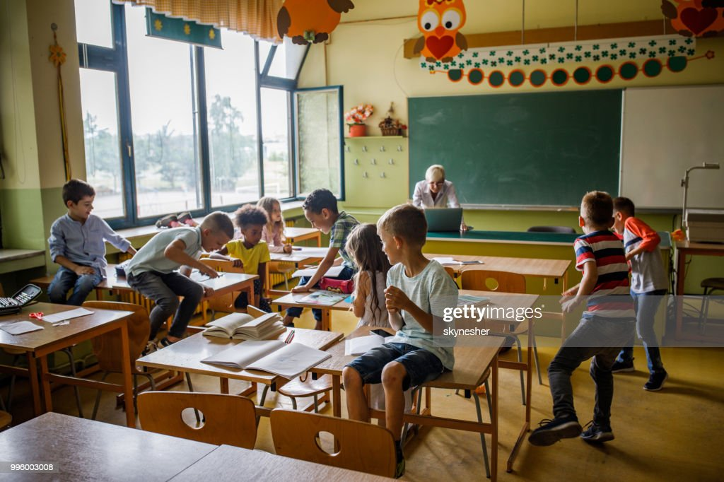 Large group of elementary students having fun on a class in the classroom. : Stock Photo