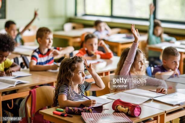große gruppe der grundschüler, die arme in die klassenzimmer. - grundschulzeit stock-fotos und bilder