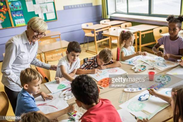 große gruppe der grundschüler mit ihrem lehrer auf kunst-klasse. - grundschule stock-fotos und bilder