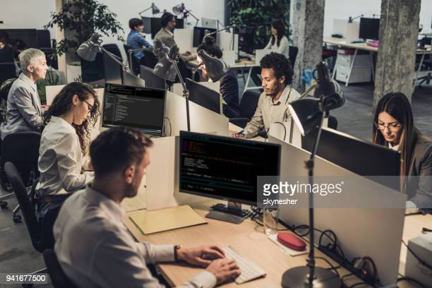large group of engineers working on computers at corporate office. - large group of people stock pictures, royalty-free photos & images