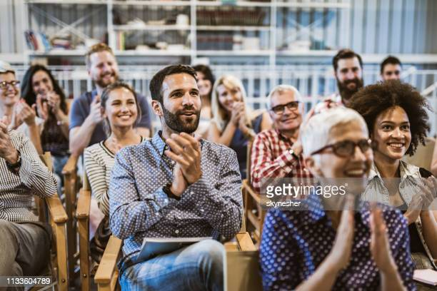 large group of entrepreneurs applauding their colleague after seminar in board room. - conference stock pictures, royalty-free photos & images