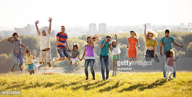 Large group of excited people jumping at the park.