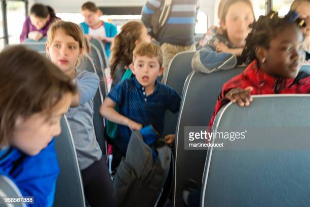 Large group of exited kids on school bus.