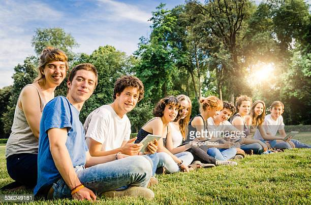 large group of friends at the park together using tablet - new generation stock pictures, royalty-free photos & images