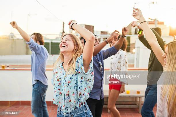 Large group of friends dancing and celebrating a rooftop party.
