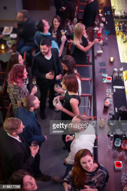 Large group of friends in bar having drinks