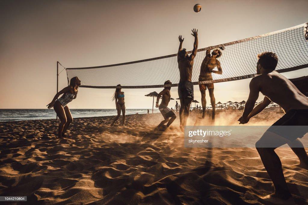Große Gruppe von Freunden spielen Beach-Volleyball bei Sonnenuntergang. : Stock-Foto