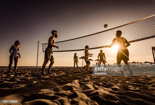 große gruppe von freunden spielen beach-volleyball bei sonnenuntergang. - strandvolleyball spielerin stock-fotos und bilder