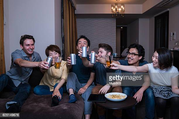 Large group of friends watching sports on TV with beer