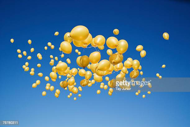 Large group of golden balloons in clear sky