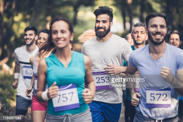 large group of happy athletes having a marathon race in nature. - marathon stock pictures, royalty-free photos & images