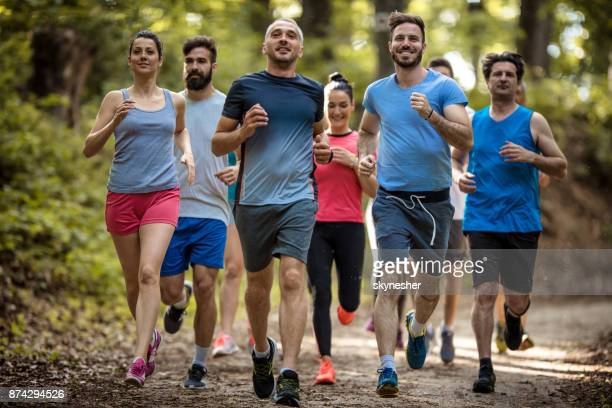 Large group of happy athletes running a marathon race in nature.