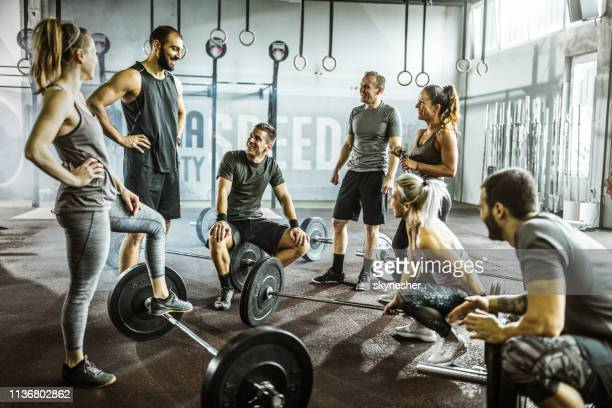 large group of happy athletic friends talking on a break in a gym. - crossfit stock pictures, royalty-free photos & images