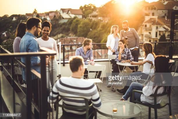 große gruppe glücklicher geschäftsleute, die nach der arbeit auf einem balkon kommunizieren. - feierabend stock-fotos und bilder