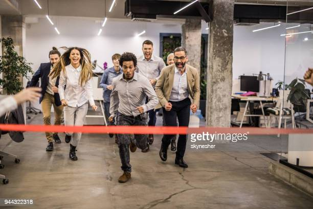 Large group of happy business people having fun while having a race at casual office.