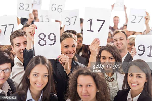 Large group of happy business people holding auction numbers.