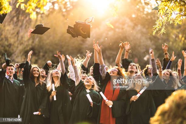large group of happy college students celebrating their graduation day outdoors. - alumni stock pictures, royalty-free photos & images