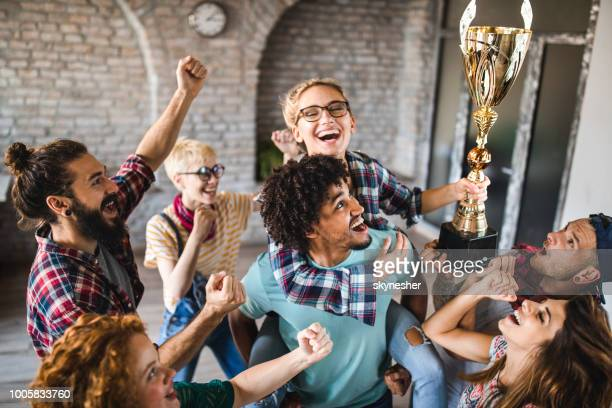 Large group of happy creative people celebrating getting a trophy at casual office.