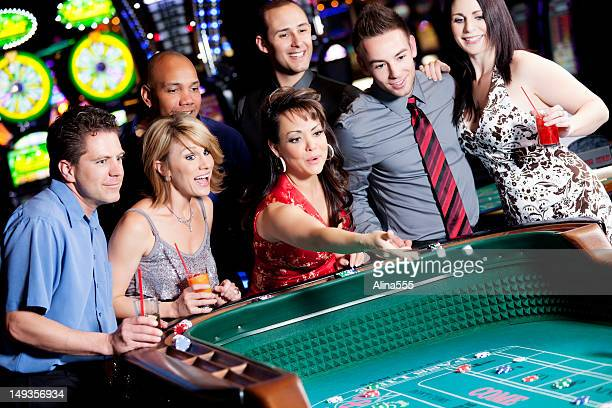 Large group of happy diverse people at the craps table