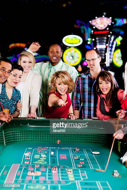 large group of happy diverse people at the craps table - casino stock photos and pictures