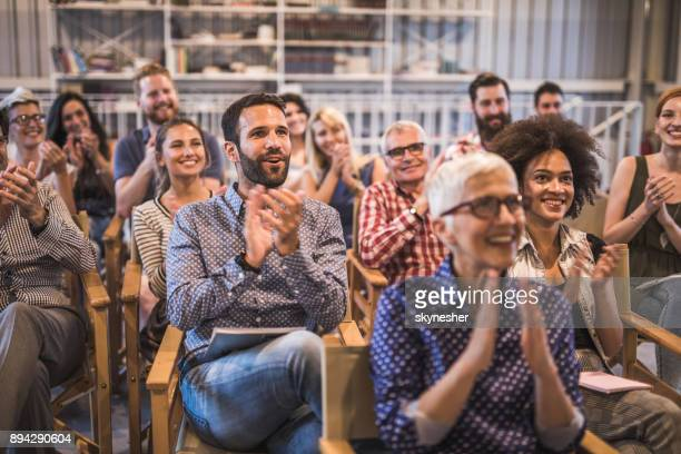 Large group of happy entrepreneurs applauding on a business seminar in a board room.