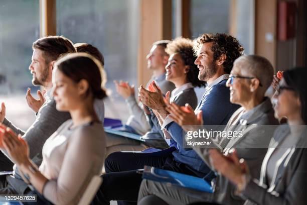 große gruppe glücklicher unternehmer applaudiert auf einem seminar im boardroom. - frauen über 30 stock-fotos und bilder
