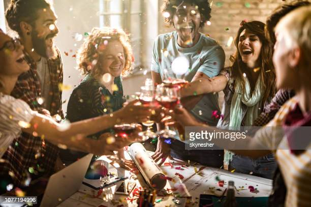 large group of happy entrepreneurs toasting at office party. - work party stock pictures, royalty-free photos & images
