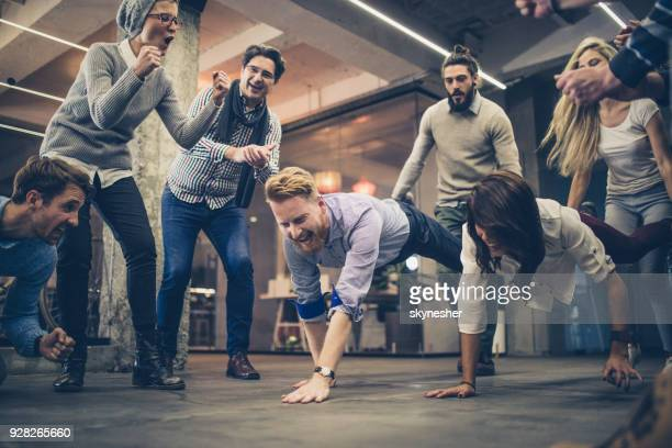 Large group of happy freelancers having fun while having wheelbarrow race at casual office.