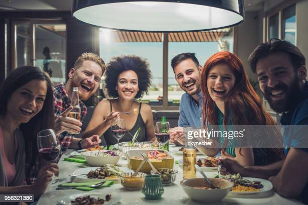 Large group of happy friends enjoying on a dinner party at dining table.