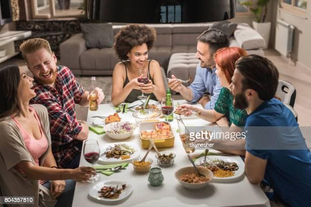 Grand groupe d'amis heureux s'amuser tout en parlant sur un repas de fête.