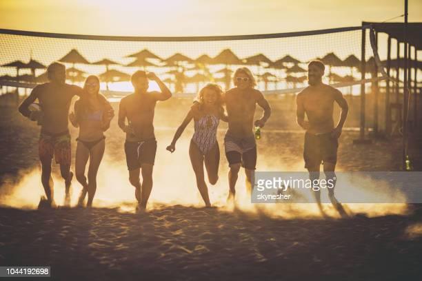 große gruppe der happy friends laufen am strand bei sonnenuntergang. - strand volleyball stock-fotos und bilder