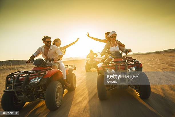 Large group of happy people driving quad bikes at sunset.