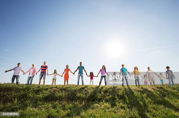 Large group of happy people holding hands against the sky.