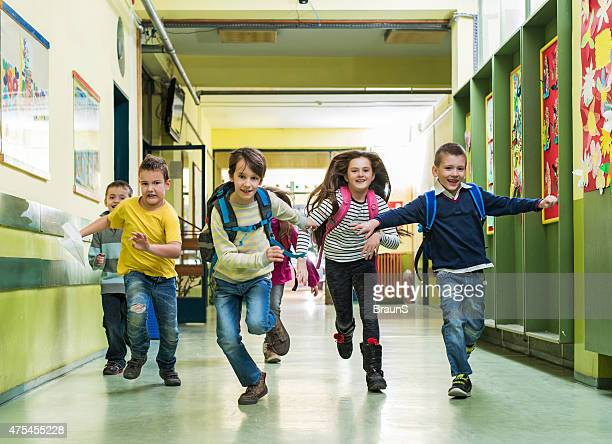 Large group of happy school children running in the hall.
