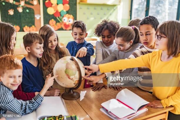 教室で地球を分析する幸せな学生の大きなグループ。 - 自然地理学 ストックフォトと画像