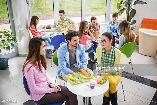 Large group of happy students communicating on a lunch break.
