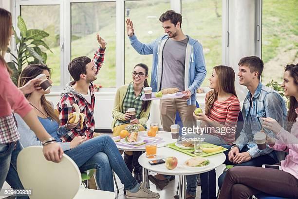 Grand groupe de étudiants heureux dans la cafétéria durant la pause déjeuner.