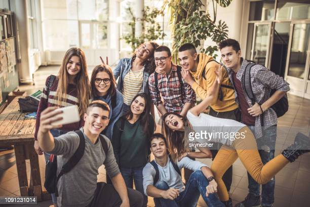 large group of happy students taking a selfie with cell phone at school. - adolescência imagens e fotografias de stock