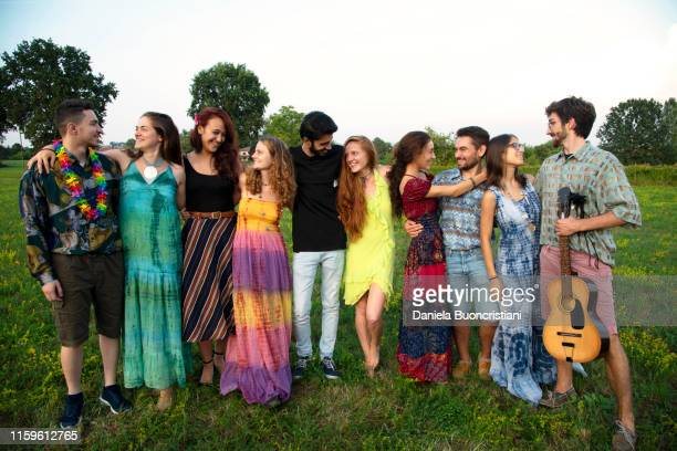 large group of happy young adults standing in field with arms around each other - long dress stock pictures, royalty-free photos & images