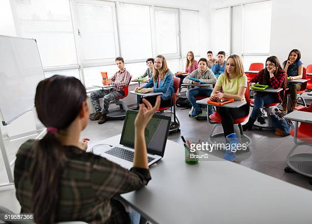 Large group of high school students attending a modern class.