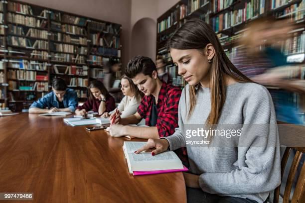 Große Gruppe von Schülerinnen und Schüler lernen in der Bibliothek.