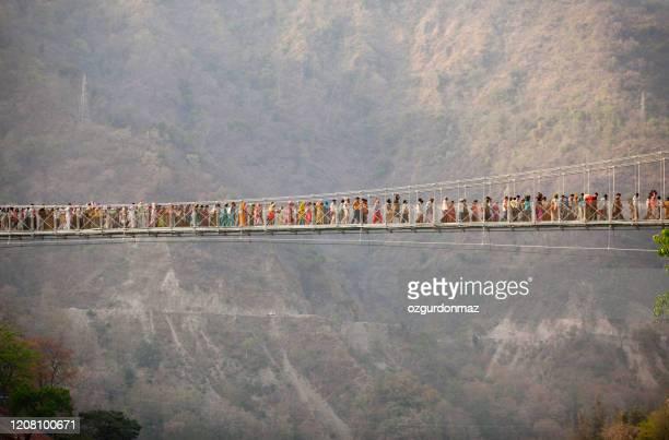 large group of hindu pilgrims passing the bridge during kumbh mela, rishikesh india - kumbh mela stock pictures, royalty-free photos & images
